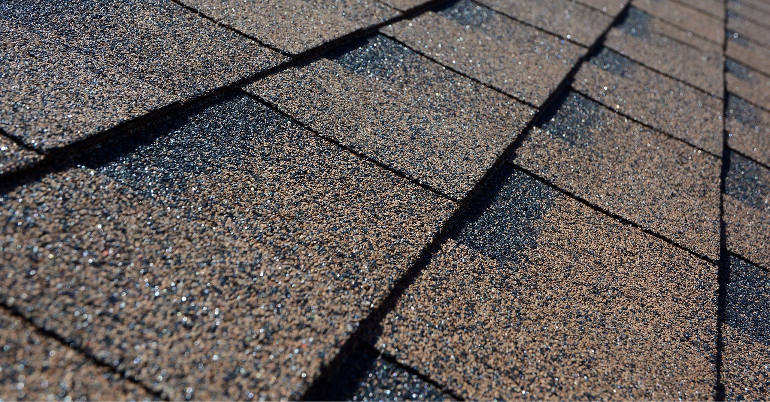 A close-up macro shot of Asphalt roof shingles, showcasing our pristine roof replacement work as a leading Denver roofing company.
